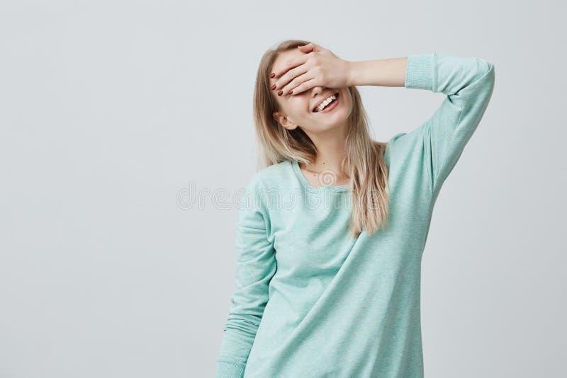 A mulher feliz com os olhos de fechamento do cabelo louro com a mão que vai ver a surpresa preparou-se pelo noivo que está e que  imagens de stock