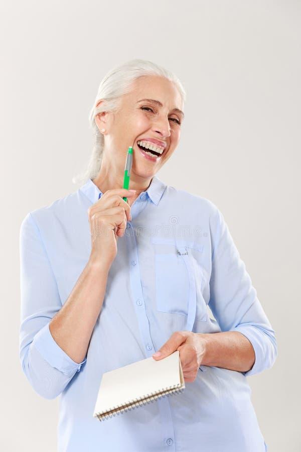 Mulher feliz com pena e caderno que olha a câmera e o sorriso imagens de stock