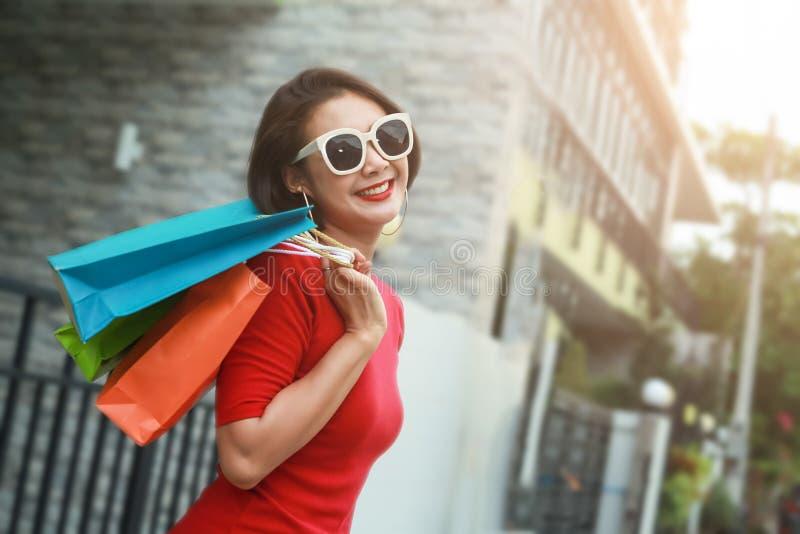Mulher feliz com sacos de compras que aprecia na compra exterior foto de stock