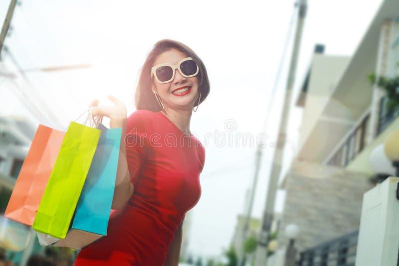 Mulher feliz com sacos de compras que aprecia na compra exterior fotos de stock royalty free