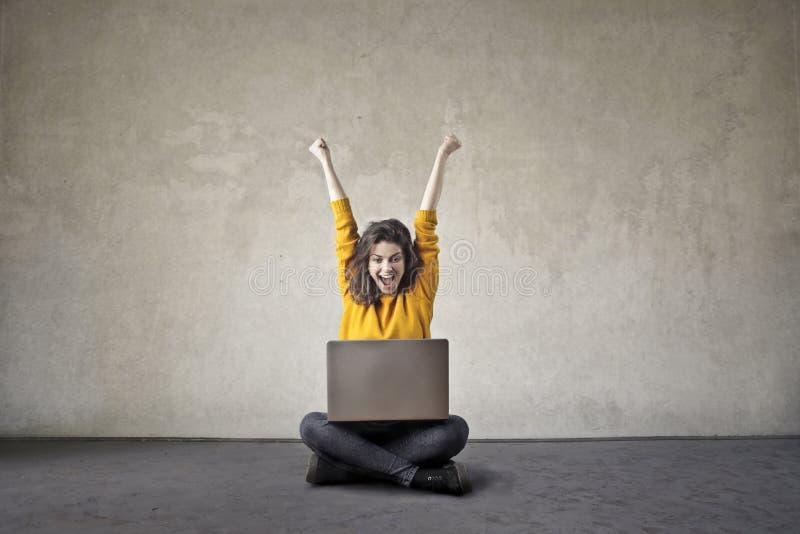 Mulher feliz com um computador imagem de stock