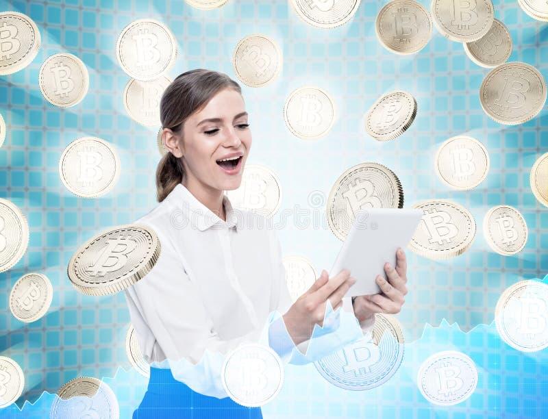 Mulher feliz com uma tabuleta, bitcoins fotos de stock