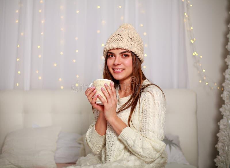 Mulher feliz com xícara de café ou chá em casa no quarto fotografia de stock royalty free