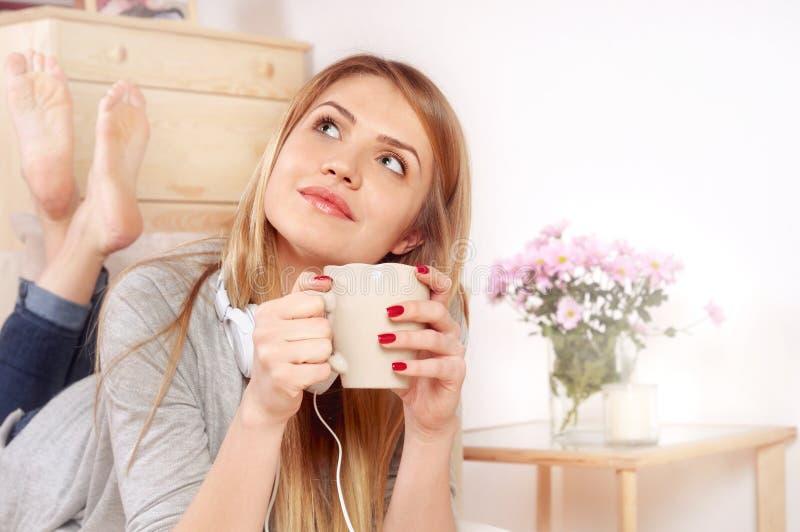 Mulher feliz com xícara de café ou chá que encontra-se no quarto fotos de stock