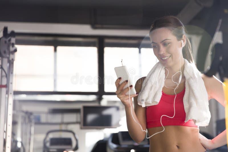 Mulher feliz da aptidão que usa o smartphone no gym fotos de stock
