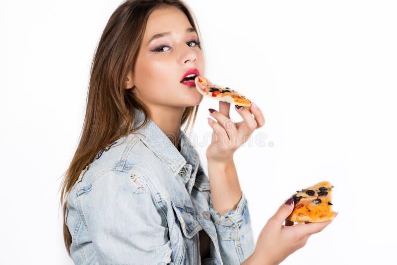 Mulher feliz da forma que guarda uma parte de pizza Menina que come a pizza fotos de stock