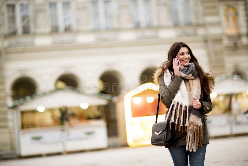Mulher feliz da forma que usa um telefone esperto na rua fotos de stock royalty free