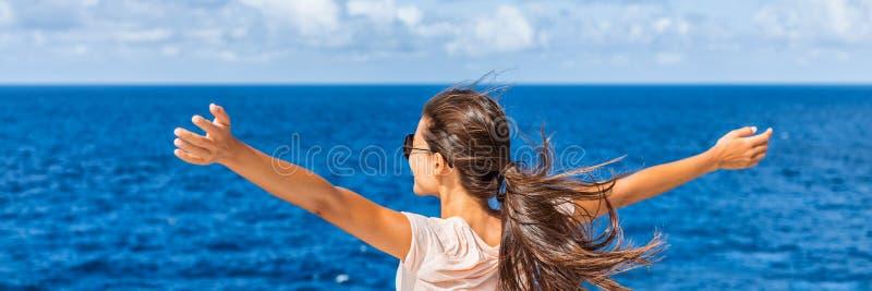 Mulher feliz da liberdade com os braços abertos que olham o mar imagens de stock