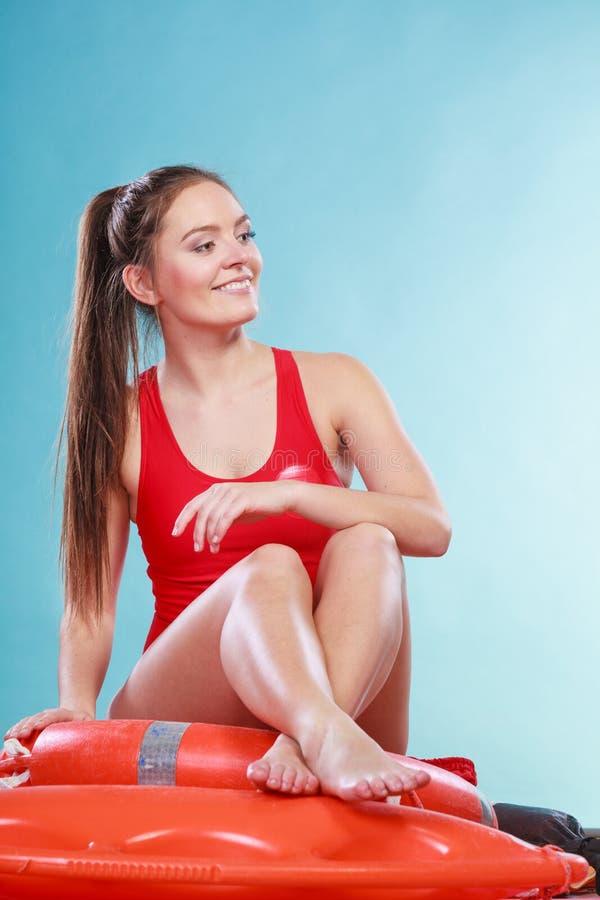 Mulher feliz da salva-vidas que senta-se na boia de anel do salvamento foto de stock