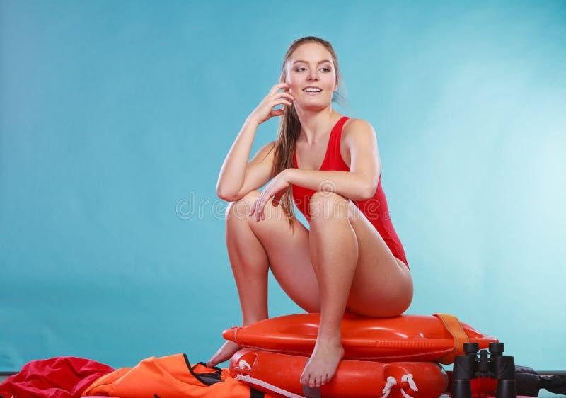 Mulher feliz da salva-vidas que senta-se na boia de anel do salvamento imagem de stock royalty free