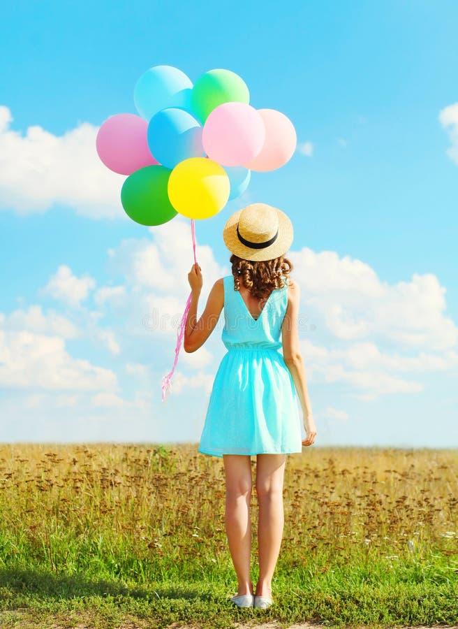 A mulher feliz da silhueta está com os balões coloridos de um ar em um chapéu de palha que aprecia um dia de verão no backgroun d imagens de stock