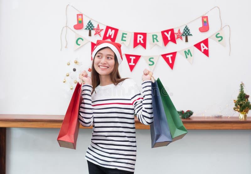Mulher feliz de Ásia do sorriso guardando muita o saco de compras no partido, compra Ch imagens de stock royalty free