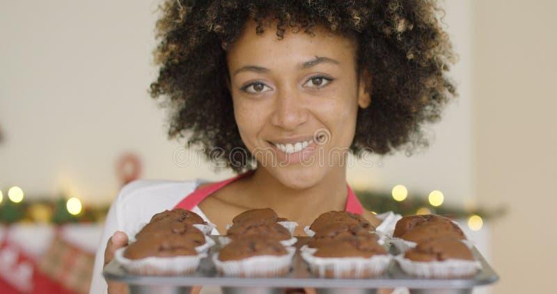 Mulher feliz de sorriso com a bandeja de queques frescos fotografia de stock
