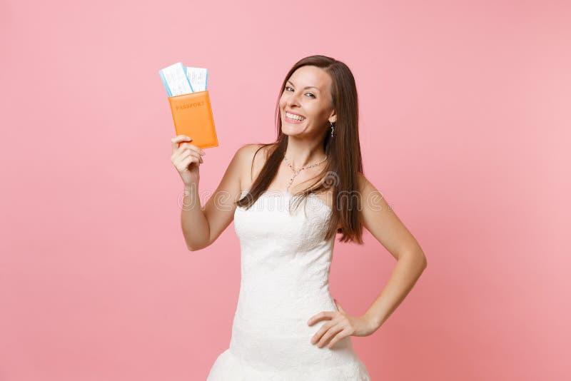 Mulher feliz de sorriso da noiva no passaporte branco da terra arrendada do vestido de casamento e no bilhete da passagem de emba imagens de stock royalty free