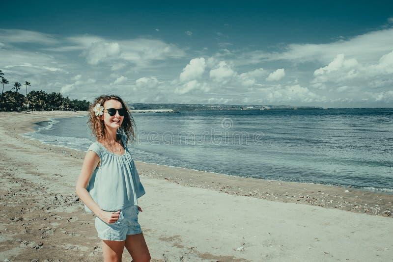 A mulher feliz de sorriso do turista aprecia férias na praia de Kuta Viajante de Bali Explore a paisagem bonita de Indonésia Curs imagens de stock
