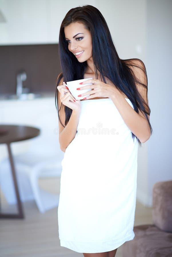 Mulher feliz de sorriso que bebe uma xícara de café imagem de stock