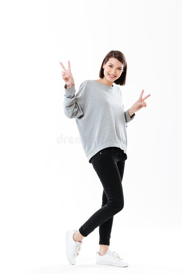 A mulher feliz de sorriso que mostra a paz gesticula com duas mãos foto de stock royalty free