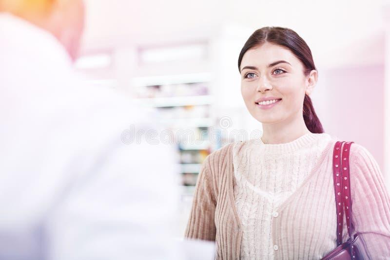 Mulher feliz de sorriso que olha o farmacêutico no uniforme branco imagem de stock royalty free