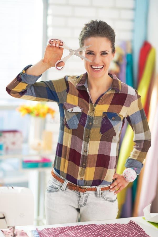 Mulher feliz do alfaiate que mostra tesouras fotos de stock royalty free