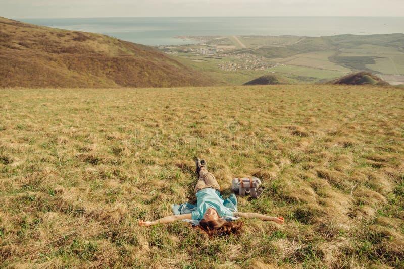 Mulher feliz do caminhante que encontra-se no prado foto de stock