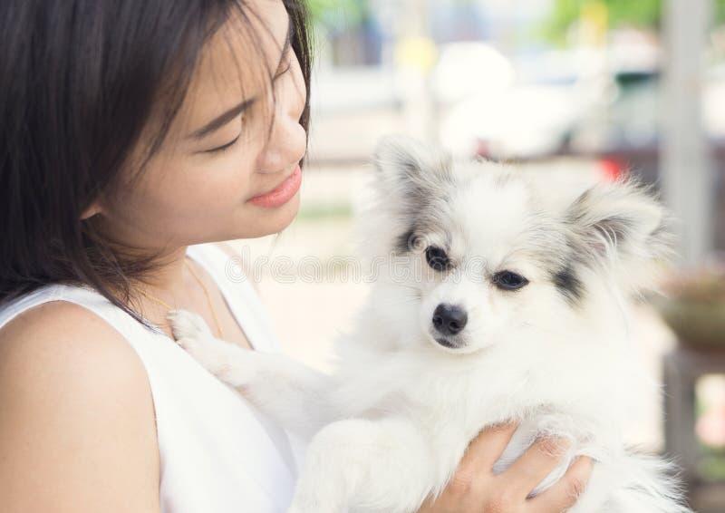 Mulher feliz do close up com o cão pomeranian branco disponível, healt do animal de estimação imagem de stock royalty free