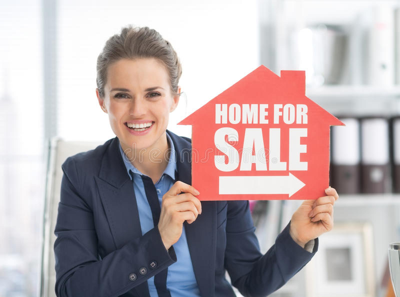 Mulher feliz do corretor de imóveis que mostra em casa para o sinal da venda imagem de stock