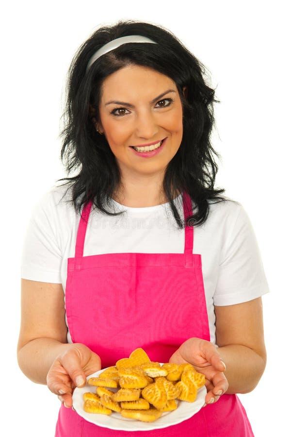 Mulher feliz do cozinheiro chefe que mostra biscoitos foto de stock