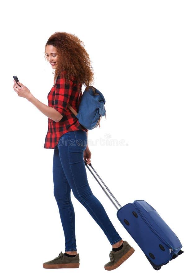 Mulher feliz do curso do corpo completo que anda com telefone celular e bagagem contra o fundo branco isolado imagem de stock