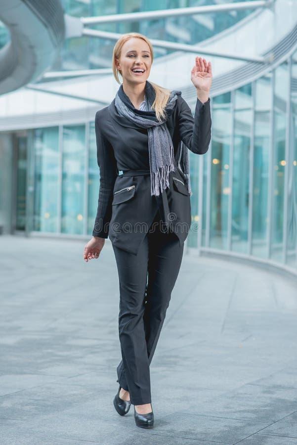 Mulher feliz do escritório que anda fora da construção imagens de stock