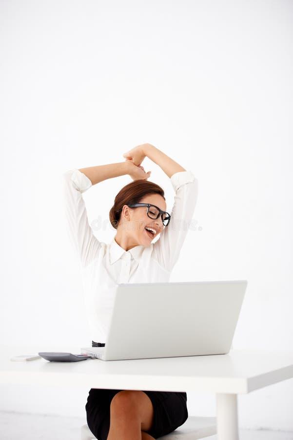 Mulher feliz do escritório que estica na parte dianteira seu portátil imagem de stock royalty free