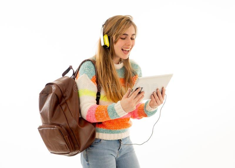 Mulher feliz do estudante nos fones de ouvido que olham a tabuleta digital que escuta a m?sica ou o curso video fotografia de stock royalty free