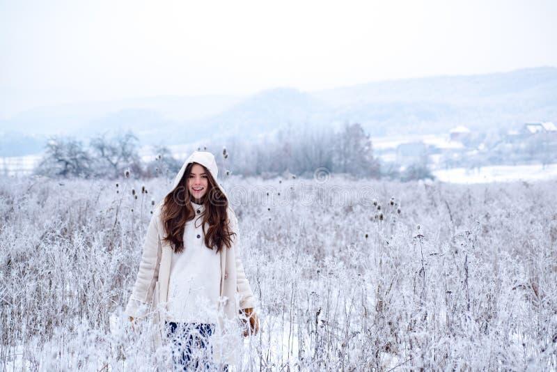 Mulher feliz do inverno sobre no fundo nevado Menina bonita exterior com a camiseta vestindo do cabelo longo que levanta na rua d foto de stock