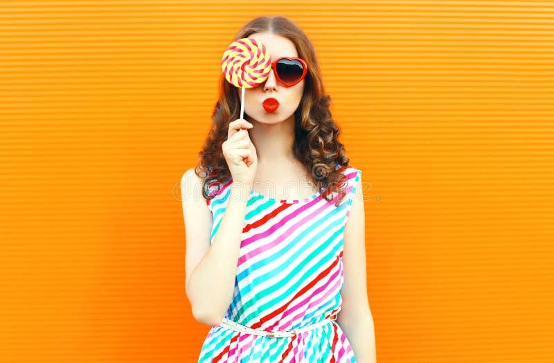 Mulher feliz do retrato que esconde seu olho com pirulito, bordos vermelhos de sopro, vestido listrado colorido vestindo na laran foto de stock royalty free