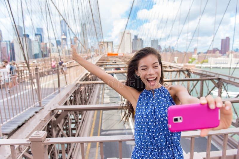 Mulher feliz do turista do selfie que toma a imagem do telefone do divertimento em Brooklyn Brige, New York imagem de stock