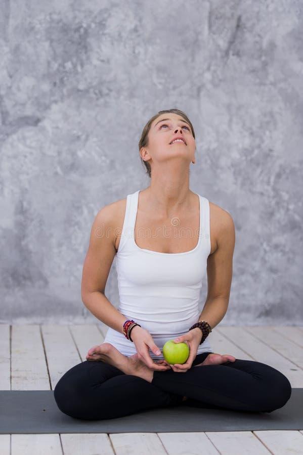 Mulher feliz dos esportes que guarda a maçã que senta-se em uma esteira da ioga sobre o fundo cinzento foto de stock royalty free