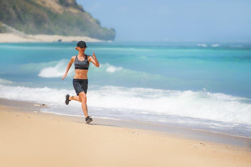 Mulher feliz e atrativa nova do corredor do esporte que faz exercício running que corre no ajuste tropical da exibição da praia d foto de stock royalty free