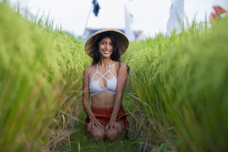 Mulher feliz e bonita nova do latino em 'sexy' de levantamento alegre de sorriso do chapéu asiático tradicional do fazendeiro iso imagem de stock royalty free