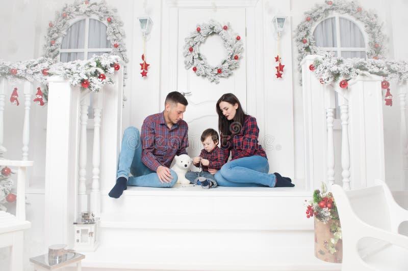 Mulher feliz e criança novas do pai de família que guardam o presente do Natal em decorações do ano novo feliz imagem de stock