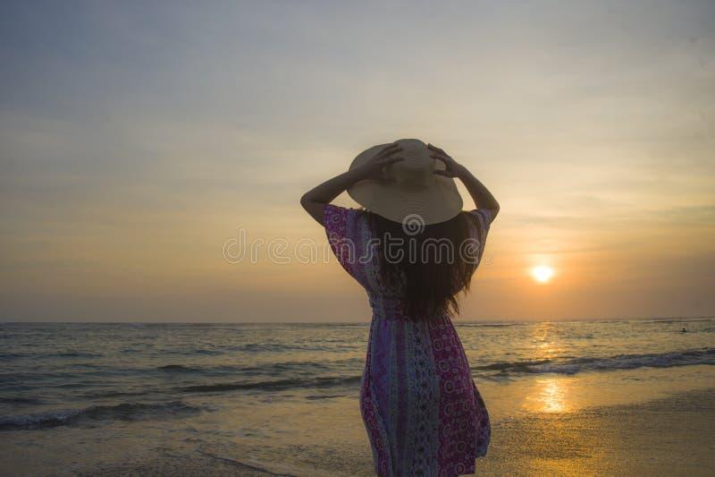Mulher feliz e relaxado nova no chapéu do verão que olha o sol sobre o mar durante um por do sol bonito surpreendente em paradis  fotos de stock