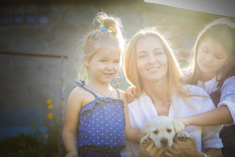 Mulher feliz e suas filhas com o cachorrinho de Labrador fotografia de stock