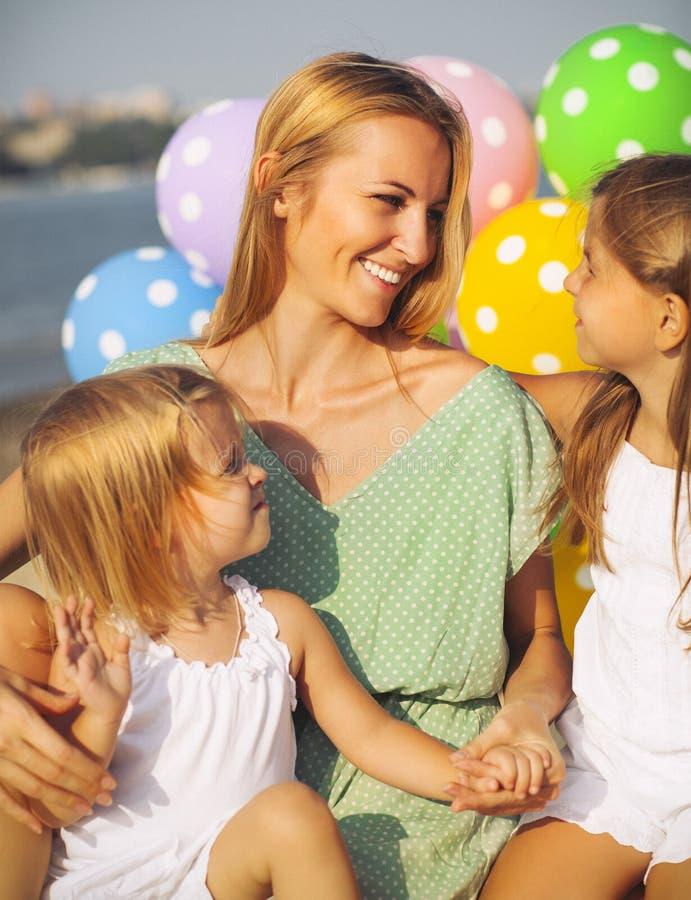 Mulher feliz e suas filhas pequenas na praia com ballons imagem de stock