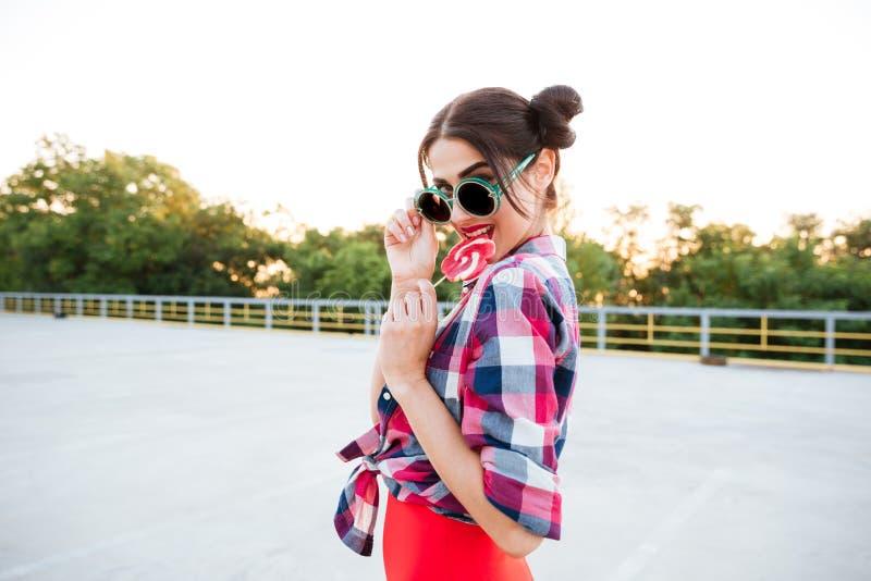 Mulher feliz em óculos de sol redondos que come o pirulito fora foto de stock