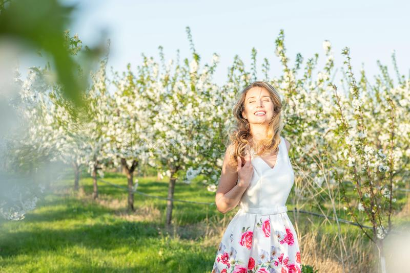 Mulher feliz em um pomar na primavera Apreciando o dia morno ensolarado Vestido retro do estilo Árvores de cereja de florescência fotos de stock royalty free