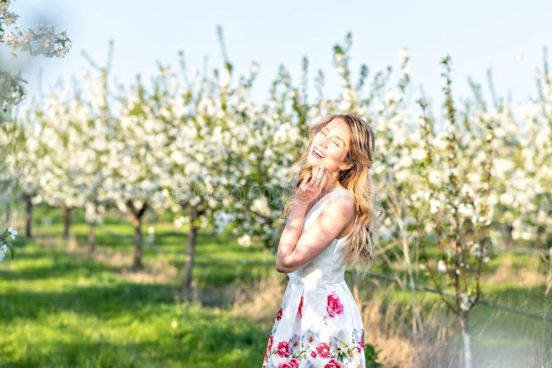 Mulher feliz em um pomar na primavera Apreciando o dia morno ensolarado Vestido retro do estilo Árvores de cereja de florescência imagem de stock royalty free