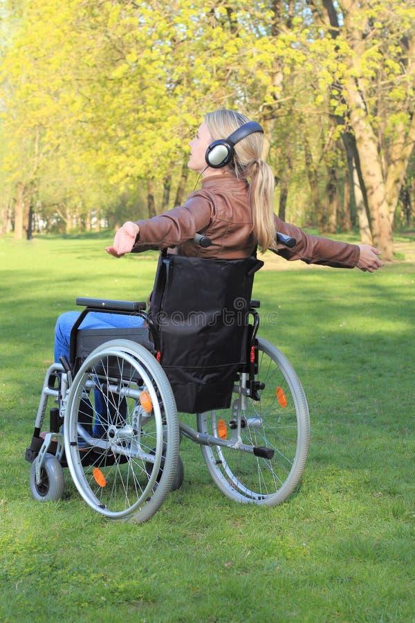 Mulher feliz em uma cadeira de rodas com propagação dos braços imagens de stock
