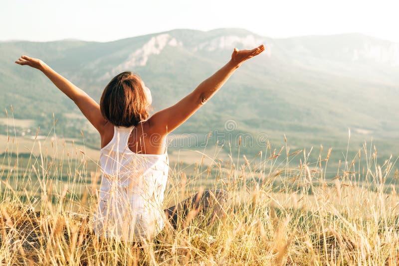 A mulher feliz encontra o nascer do sol na montanha imagem de stock royalty free
