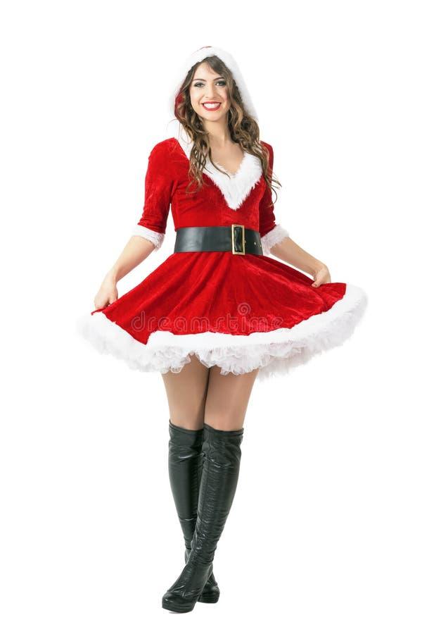 Mulher feliz entusiasmado de Santa que está com pés cruzados e que guarda o vestido fotos de stock royalty free