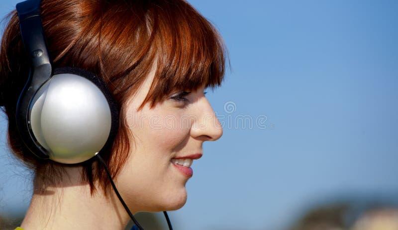 A mulher feliz escuta música fotografia de stock