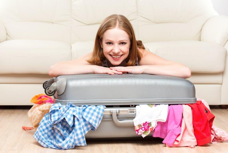 A mulher feliz está embalando a mala de viagem em casa imagem de stock