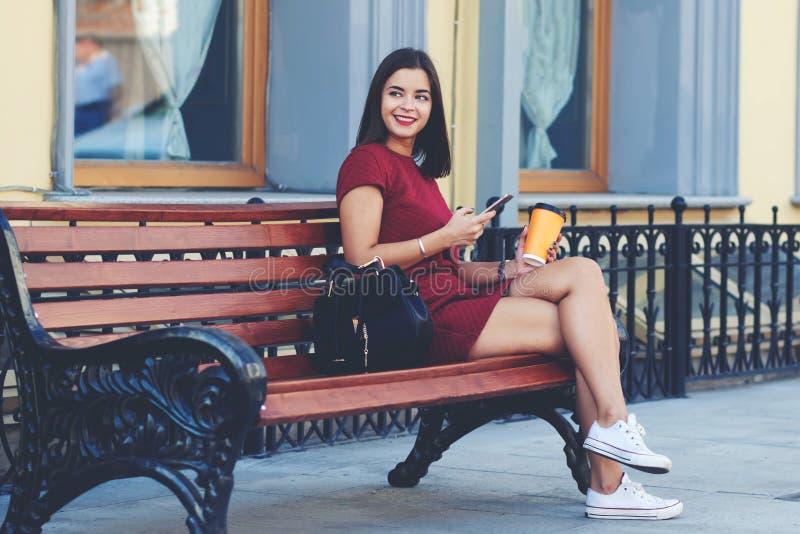 A mulher feliz está esperando chama seu telefone celular, quando relaxar fora com café fotografia de stock royalty free